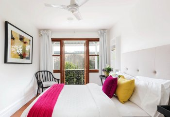 bedroom-with-balcony-occasional-chair-and-pink-accessories