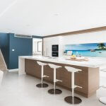 a-kitchen-island-bench-with-white-bar-stools-and-a-ocean-splashback
